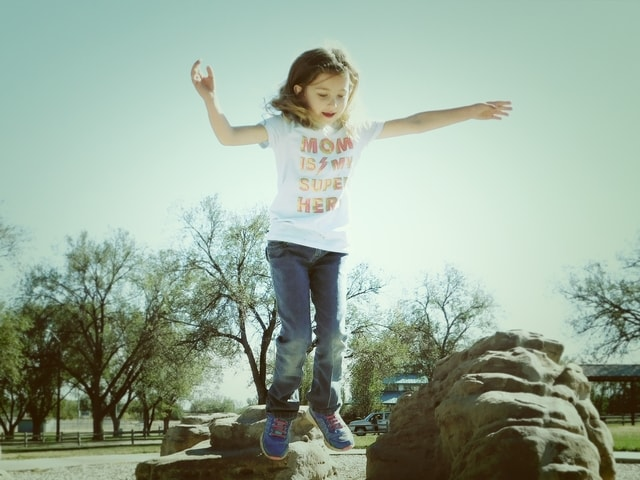 little-girl-jumping-from-a-rock picture material