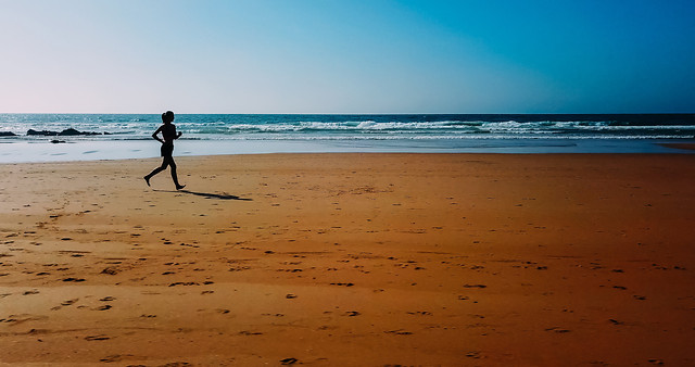 aerial-drone-view-of-healthy-sportive-woman-running-on-beach-near-ocean 图片素材
