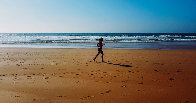 aerial-drone-view-of-healthy-sportive-woman-running-on-beach-near-ocean picture material