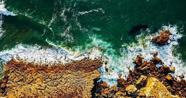 aerial-view-from-flying-drone-of-ocean-waves-crushing-on-rocky-beach-landscape picture material