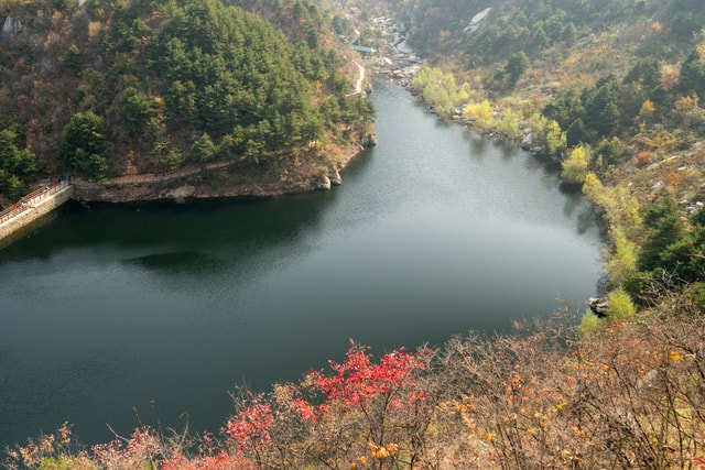 two-yellowed-mountains-cross-a-river-in-the-autumn-in-the-middle-of-two-yellowed-mountains-in-autumn 图片素材